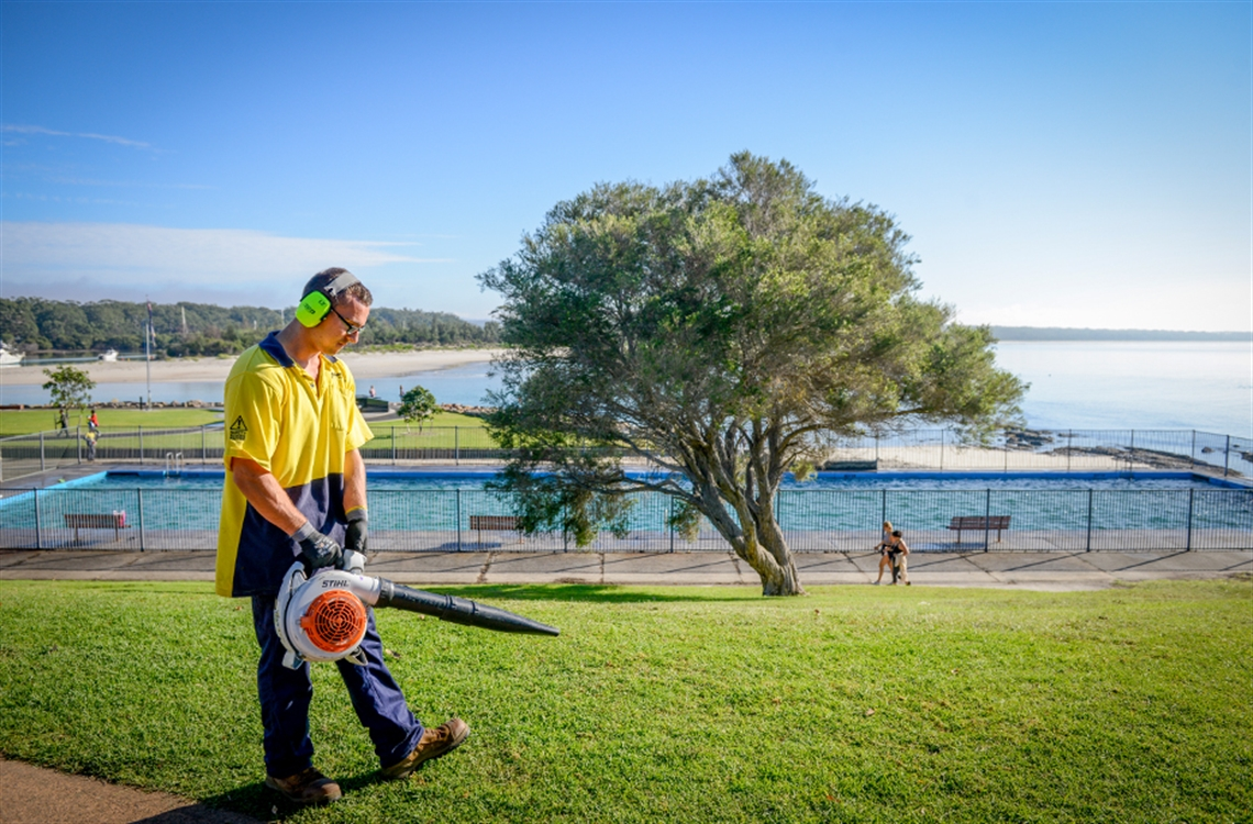 Shoalhaven City Council employee in high vis using a leaf blower to clear a grassed area in front of Huskisson ocean pool