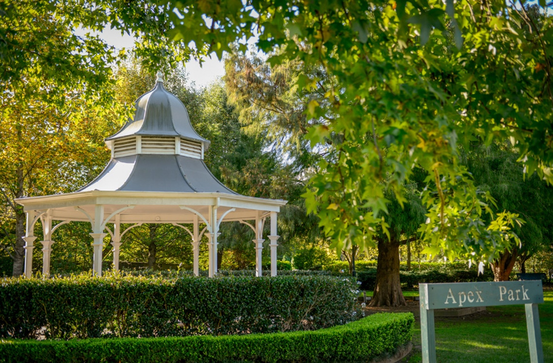 A circular gazebo surrounded by a box hedge and trees in park