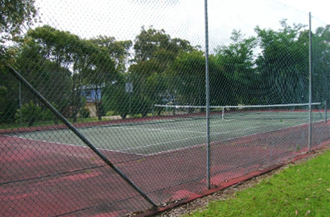 Single concrete tennis court surrounded by fencing and bordered by trees in the background